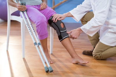 Image of one person sitting down holding crutches and one person checking knee brace